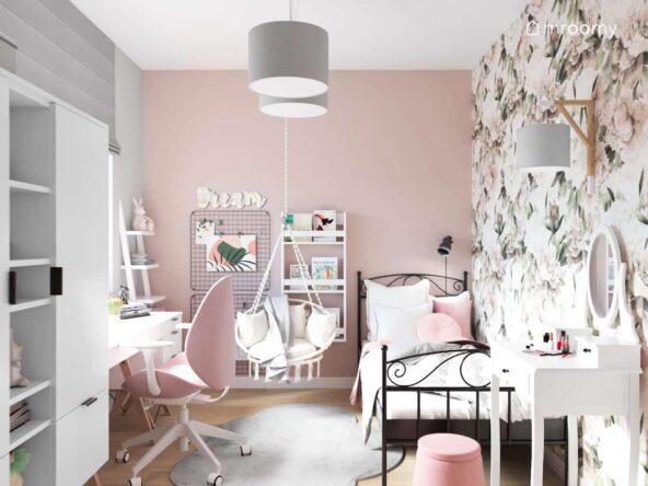 Pokój dla dziewczynki z przewagą różu i bieli oraz szarymi dodatkami a w nim metalowe łóżko białe półki i regały czarne organizery na ścianach i fotel wiszący