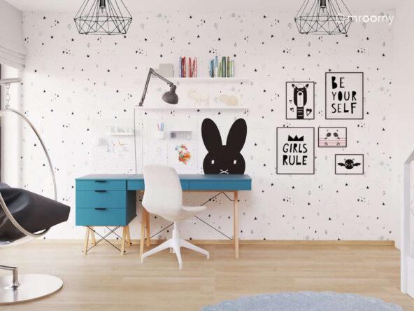 Strefa nauki z niebieskim biurkiem z kontenerkiem oraz półkami i organizerami ściennymi oraz ściana ozdobiona plakatami w ramkach i tapetą w minimalistyczne symbole w pokoju dla dziewczynki