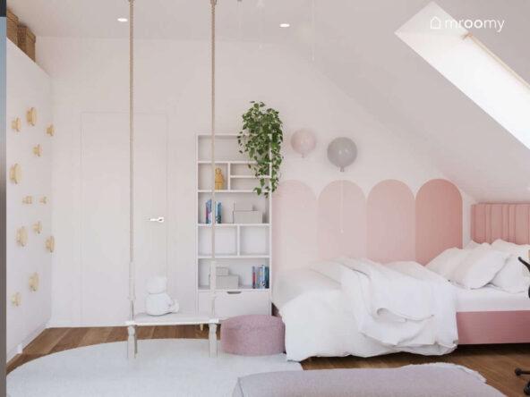 Biały pokój dla dziewczynki z wyrazistymi różowymi dodatkami w postaci łóżka i fragmentu ściany oraz z huśtawką wiszącą i szafą uzupełnioną uchwytami ze sklejki