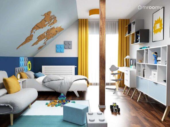 Biało szaro niebieski pokój dla chłopca z drewnianą mapą świata na skosie panelami ściennymi w kształcie klocków oraz białymi meblami i żółtymi dodatkami