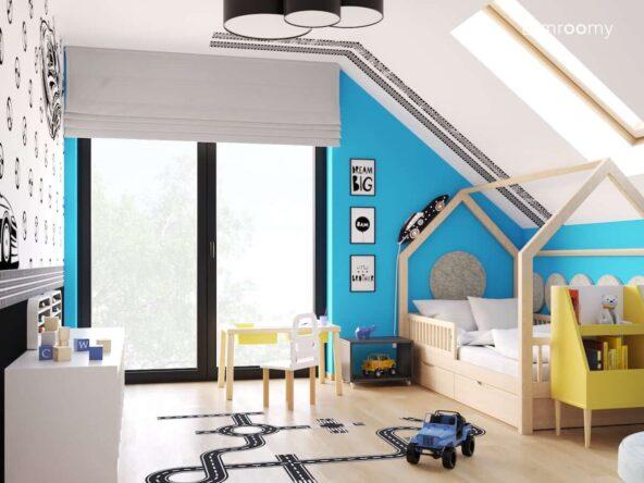 Biało niebieski pokój dla chłopca z drewnianym łóżkiem domkiem stolikiem do zabawy z krzesełkiem z oparciem w kształcie auta oraz lampką nocną w kształcie wyścigówki