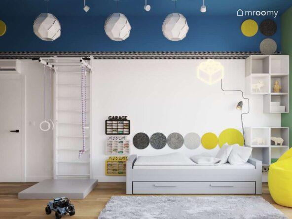 Biało niebieski pokój dla chłopca z łóżkiem z szufladą drabinką gimnastyczną i materacem oraz piętrowymi półkami na samochody a także z białymi lampami sufitowymi w geometrycznym kształcie
