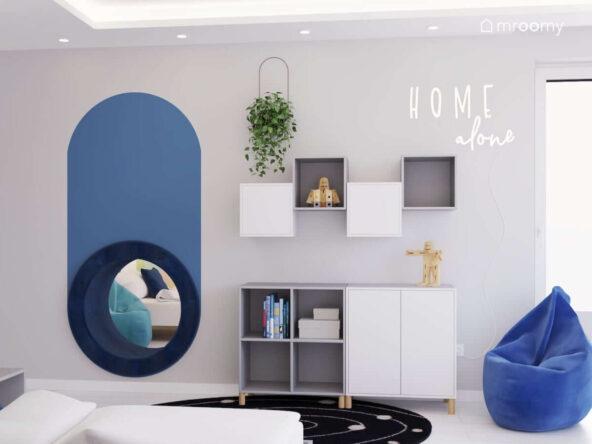 Biało szary pokój dla chłopca z licznymi białymi i szarymi szafkami niebieską pufą sako ledonem w kształcie napisu oraz okrągłym przejściem do pokoju obok