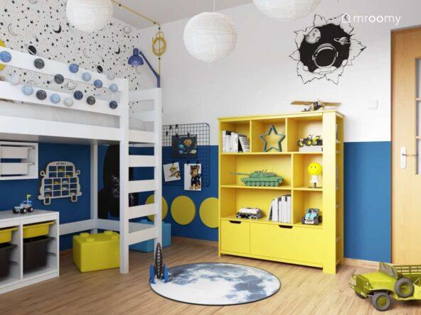 Biało niebieski kosmiczny pokój dla przedszkolaka z białymi i żółtymi meblami naklejką ścienną z kosmonautą kosmiczną tapetą a także niebieską girlandą cotton balls i półką na samochody w kształcie samochodu
