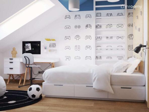 Pokój dla młodego gracza z tapetą w pady do konsoli biurkiem na drewnianych nogach oraz licznymi organizerami a także białym łóżkiem z szufladami