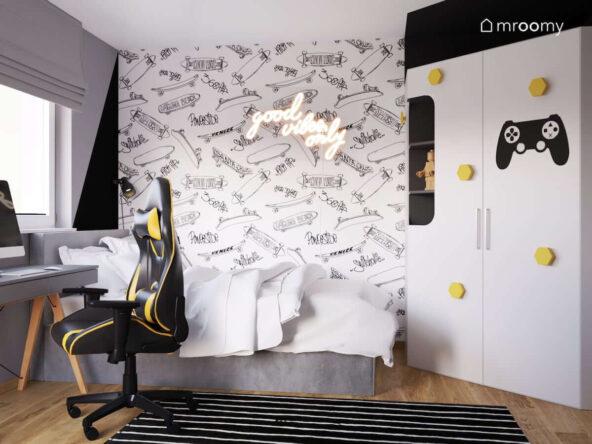 Biało czarno szary pokój dla chłopca miłośnika gier wideo i skateboardingu a w nim szare łóżko biurko z krzesłem gamingowym oraz szafa z żółtymi uchwytami i tapeta w deskorolki