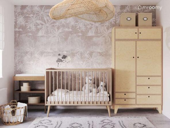 Drewniane łóżeczko z mobilem z chmurkami szafa ze sklejki a na niej kartonowe pojemniki a także drewniany przewijak i tapeta w palmy w pokoju dla noworodka