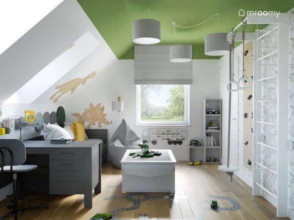 Biało zielony pokój dla chłopca na poddaszu z szarym biurkiem i łóżkiem a także pufą sako i stolikiem do zabawy oraz ozdobnymi dinozaurami ze sklejki na ścianach