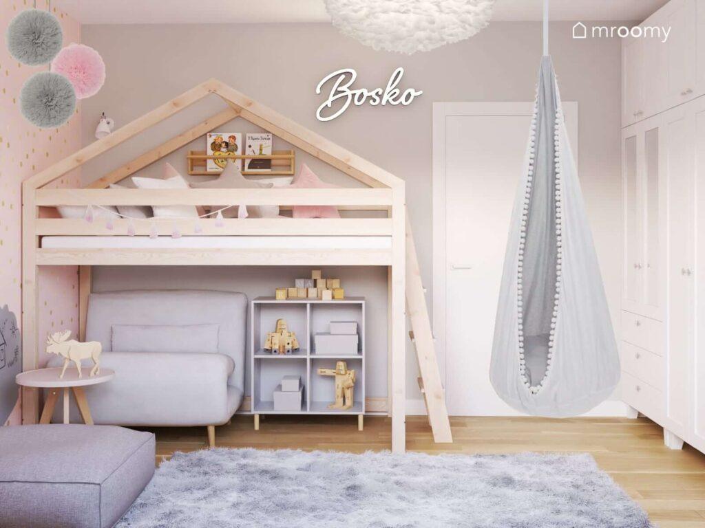Drewniane łóżko w kształcie domku a pod nim rozkładana sofa i szafka na drewnianych nóżkach a także huśtawka kokon i ledon w kształcie napisu w pokoju dla kilkulatki dziewczynki