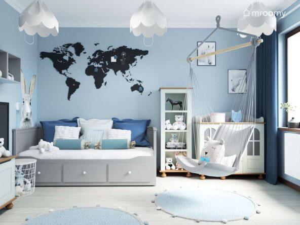 Niebieski pokój dla dziewczynki z szarym łóżkiem z szufladami białymi meblami tablicą magnetyczno kredową w kształcie mapy świata oraz wiszącym fotelem