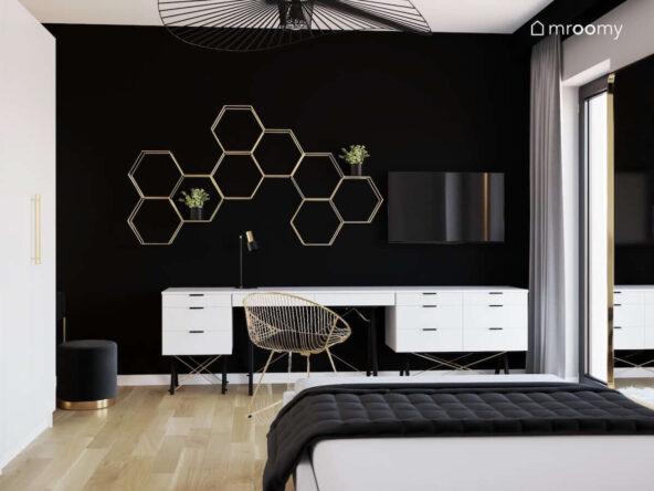 Czarno biało szary pokój dla nastolatki w stylu glamour z białym biurkiem i kontenerami oraz złotą półką ścienną w kształcie heksagonów na tle czarnej ściany