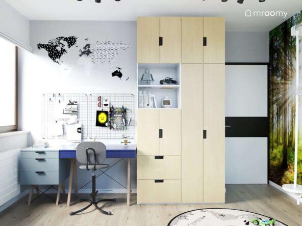 Strefa nauki w pokoju dla chłopca z biurkiem organizerami ściennymi i mapą świata a także dużą szafą