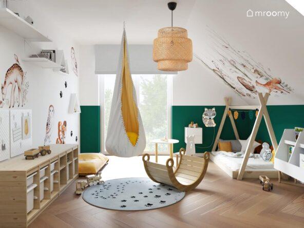 Biało zielony pokój dla chłopca z licznymi motywami zwierzęcymi drewnianym łóżkiem tipi drewnianym regałem z pojemnikami na zabawki a także bambusową lampą i wiszącym fotelem kokonem
