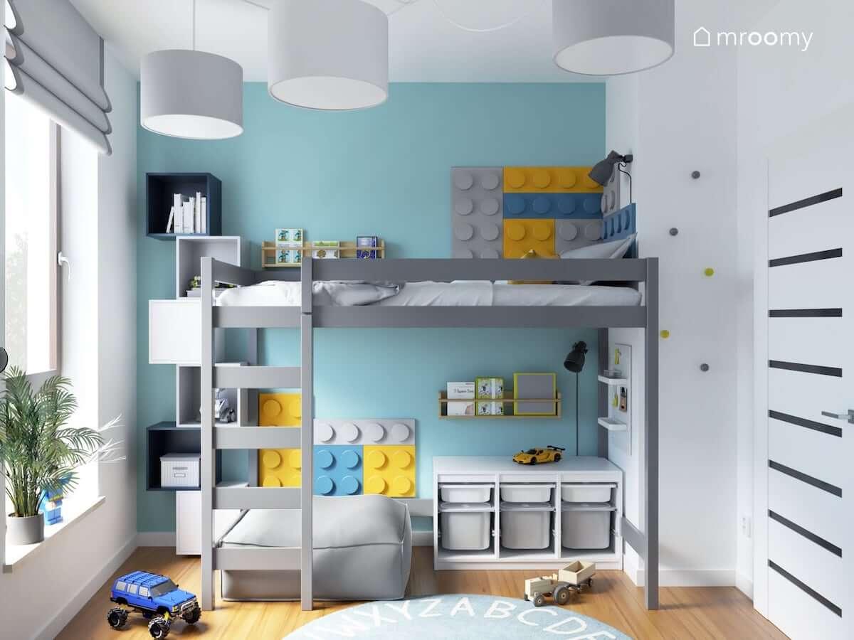 Szare łóżko na antresoli uzupełnione kolorowymi panelami ściennymi w kształcie klocków z miejscem do czytania oraz zabawy pod spodem a obok granatowe i białe szafki ścienne w biało niebieskim pokoju dla chłopca