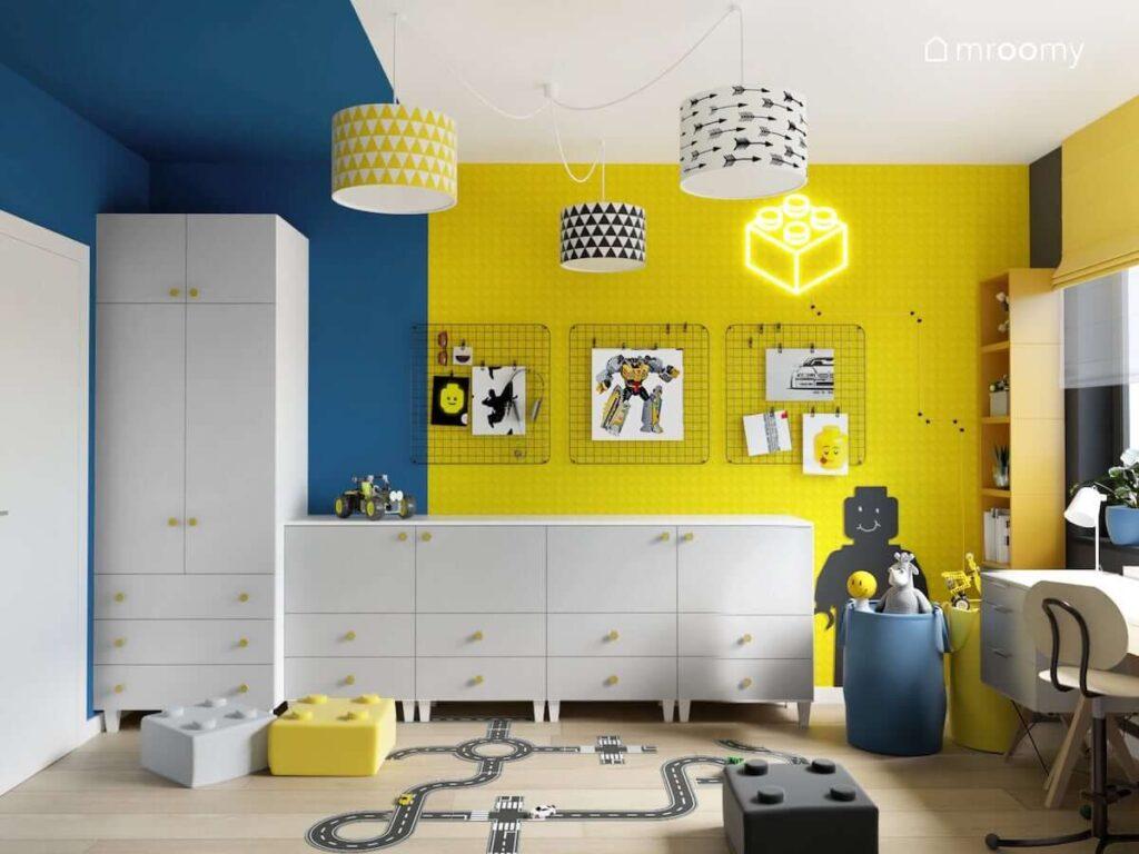 Biało niebiesko żółty pokój dla chłopca w wieku szkolnym z białą szafą modułową a także czarnymi organizerami ściennymi i lampą sufitową z ozdobnymi abażurami