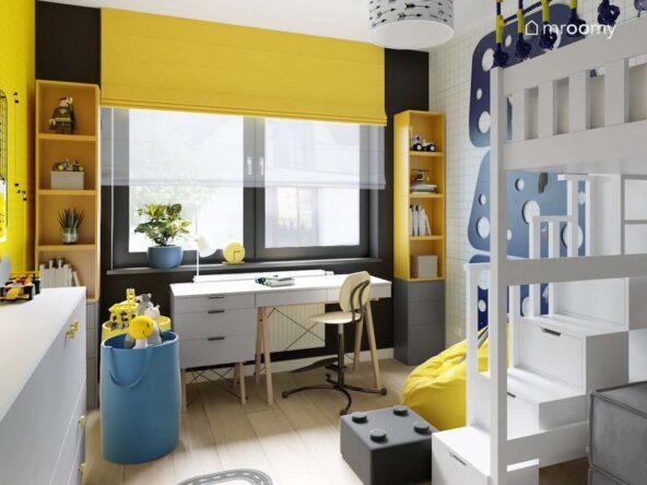 Żółto czarna strefa nauki w pokoju dla chłopca z dwoma wysokimi regałami oraz biurkiem a także koszami na zabawki w kolorze niebieskim
