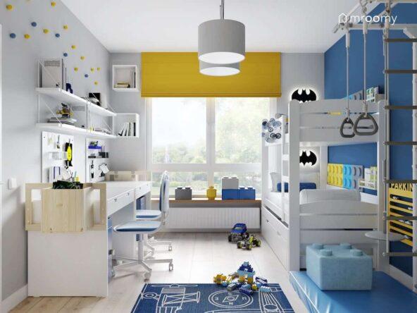 Pokój dla dwóch chłopców z białymi i niebieskimi ścianami oraz żółtymi dodatkami a także z białym łóżkiem piętrowym i strefą nauki z dwoma biurkami z drewnianymi dostawkami