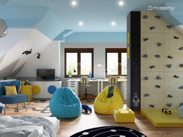 Biało niebieski pokój dla dwóch chłopców z białymi meblami oraz żółtymi i niebieskimi dodatkami a także ścianką wspinaczkową i ścianą pomalowaną farbą tablicową
