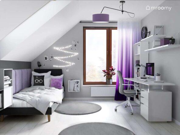 Biało szary pokój dla nastolatki z czarnym tapicerowanym łóżkiem białym biurkiem ozdobnymi lampkami LED oraz z fioletowymi akcentami w postaci poduszki lampy sufitowej i zasłon