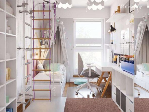 Jasny wąski pokój dla dziewczynki z drabinką gimnastyczną biurkiem oraz łóżkiem uzupełnionym ozdobnym baldachimem