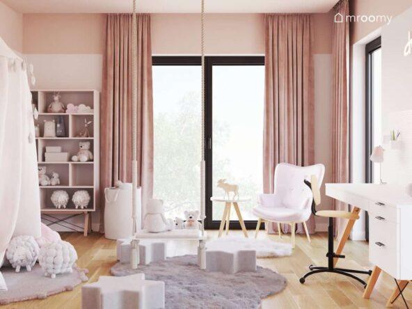 Pudrowo różowy pokój dla dziewczynki z białymi i różowymi meblami na drewnianych nogach oraz wiszącą huśtawką oraz z puszystymi dywanami na podłodze
