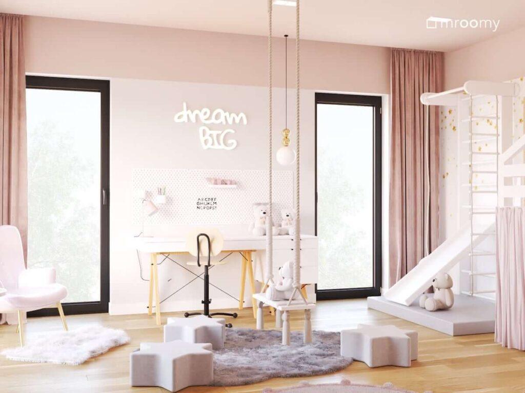 Biurko na drewnianych nogach z kontenerkiem a nad nim organizery ścienne i ledon w kształcie napisu a także huśtawka pokojowa i drabinka gimnastyczna ze zjeżdżalnią w pokoju dla dziewczynki