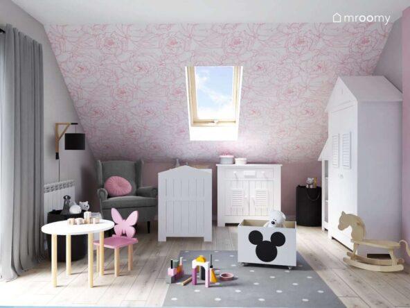 Poddaszowy pokój dla niemowlaka z białymi meblami szarym fotelem i dywanem oraz skosem ozdobionym biało różową tapetą w kwiaty
