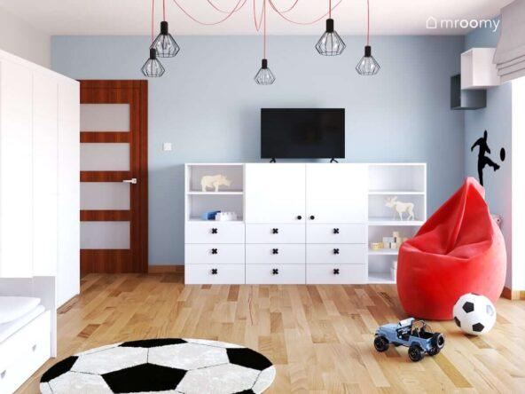 Biało niebieski pokój dla chłopca w wieku szkolnym z białymi meblami modułowymi czerwoną pufą oraz lampą sufitową na rozłożystym czerwonym zawieszeniu