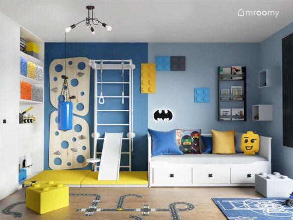 Biało niebieski pokój dla chłopca z białym łóżkiem drabinką gimnastyczną ścianką wspinaczkową i żółtymi materacami a także ze ścianą ozdobioną miękkimi panelami ściennymi w kształcie klocków