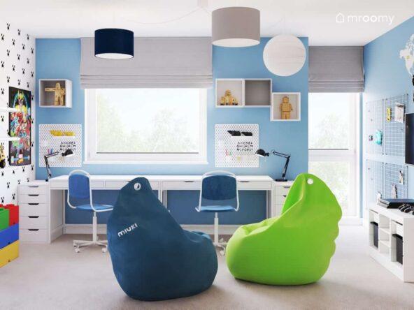Strefa nauki w biało niebieskiej bawialni dwóch chłopców z dwoma biurkami organizerami i szafkami ściennymi a także dwie wygodne pufy sako