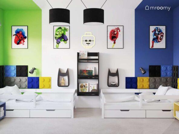 Dwa białe łóżka z szufladami oraz szafki ścienne w kształcie Batmana a także czarna biblioteczka i ozdobne plakaty z superbohaterami w pokoju dla dwóch chłopców