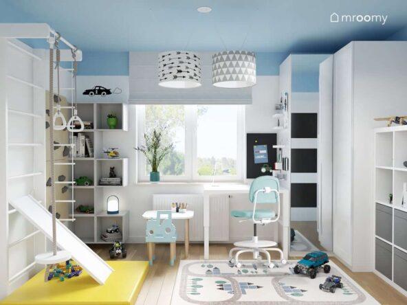 Biało niebieski pokój dla dwóch chłopców z białymi meblami oraz drabinką gimnastyczną ścianką wspinaczkową żółtym materacem i dywanem przedstawiającym miasto