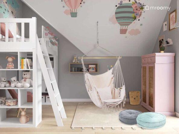 Pastelowy pokój dla dziewczynki z łóżkiem na antresoli huśtawką hamakiem oraz skosem ozdobionym naklejkami w kształcie balonów