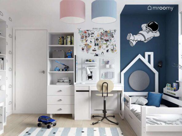 Dwukolorowy pokój dla rodzeństwa z łóżkiem ze stelażem w kształcie domku oraz biurkiem z organizerami ściennymi w części dla brata