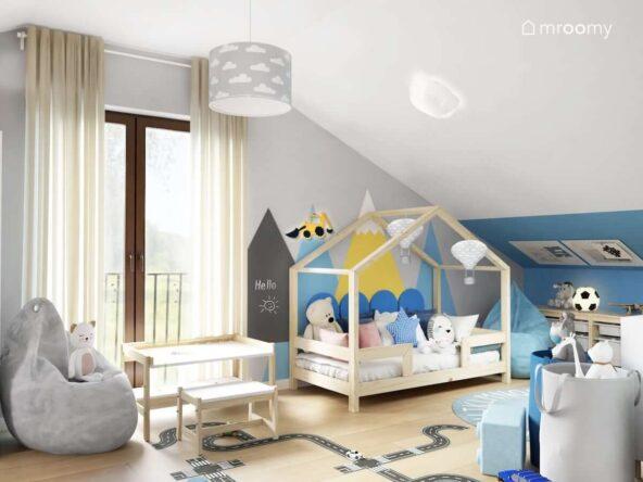 Część chłopięca w pokoju brata i siostry utrzymana w kolorze niebieskim w drewnianym domkiem w kształcie domku ozdobionym papierowymi balonami oraz ze ścianą pomalowaną w górzysty wzór