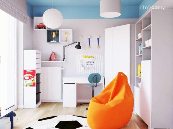 Szaro niebieski pokój dla chłopca fana piłki nożnej i figurek Super Zings z białymi meblami pomarańczową pufą sako i dywanem w kształcie piłki