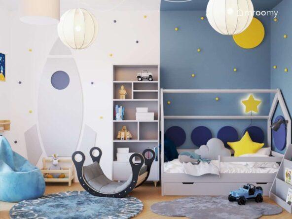 Biało niebieski pokój dla niemowlaka z czarnym bujakiem tablicą kredową w kształcie rakiety oraz z łóżkiem w kształcie domku uzupełnionym panelami ściennymi oraz gwiezdnymi dodatkami