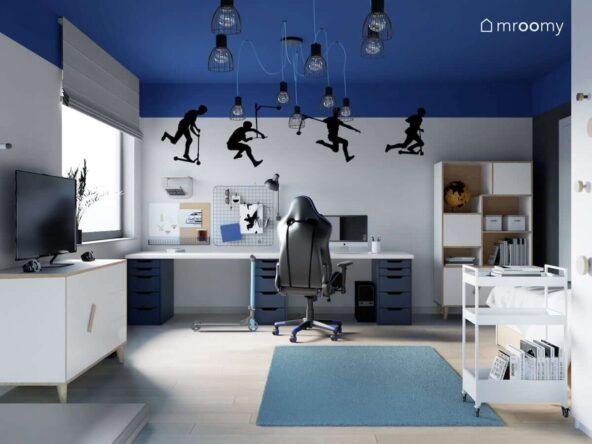 Niebiesko szary pokój dla miłośnika jazdy na hulajnodze z dużym biurkiem z organizerami biało drewniamnymi meblami naklejkami ściennymi i rozłożystymi lampami sufitowymi