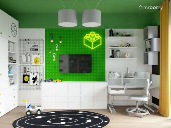 Strefa nauki z biurkiem z nadstawką oraz półkami ściennymi a także niska komoda i organizery ścienne oraz ściana oklejona zieloną naklejką we wzór klocka Lego w pokoju dla chłopca