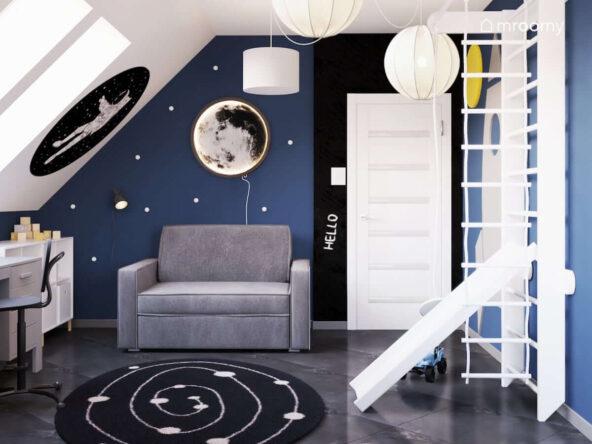 Kosmiczny poddaszowy pokój dla chłopca z rozkładaną sofą drabinką gimnastyczną ze zjeżdżalnią i kinkietem w kształcie księżyca