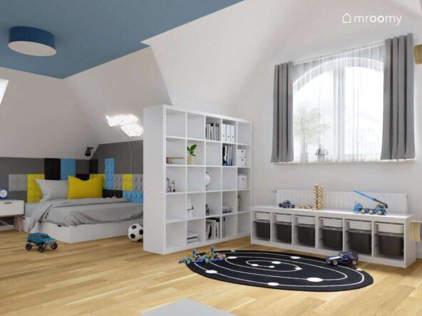 Jasny pokój dla chłopca z niebieskim sufitem oraz białymi meblami i łóżkiem uzupełnionym panelami ściennymi w kształcie klocków