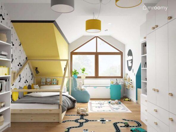 Biało żółty pokój dla chłopca z drewnianym łóżkiem domkiem niebieskimi dodatkami i naklejką podłogową w kształcie jezdni