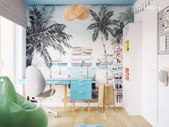 Strefa nauki w pokoju dla chłopca w wieku szkolnym a w niej niebieskie biurko i kontenerek wakacyjna tapeta oraz bambusowa lampa podłogowa