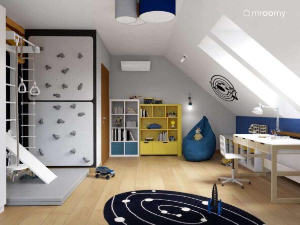 Poddaszowy pokój dla chłopca z drabinką gimnastyczną ścianką wspinaczkową białym i żółtym regałem biurkiem z drewnianymi szufladkami i czarno białym dywanem