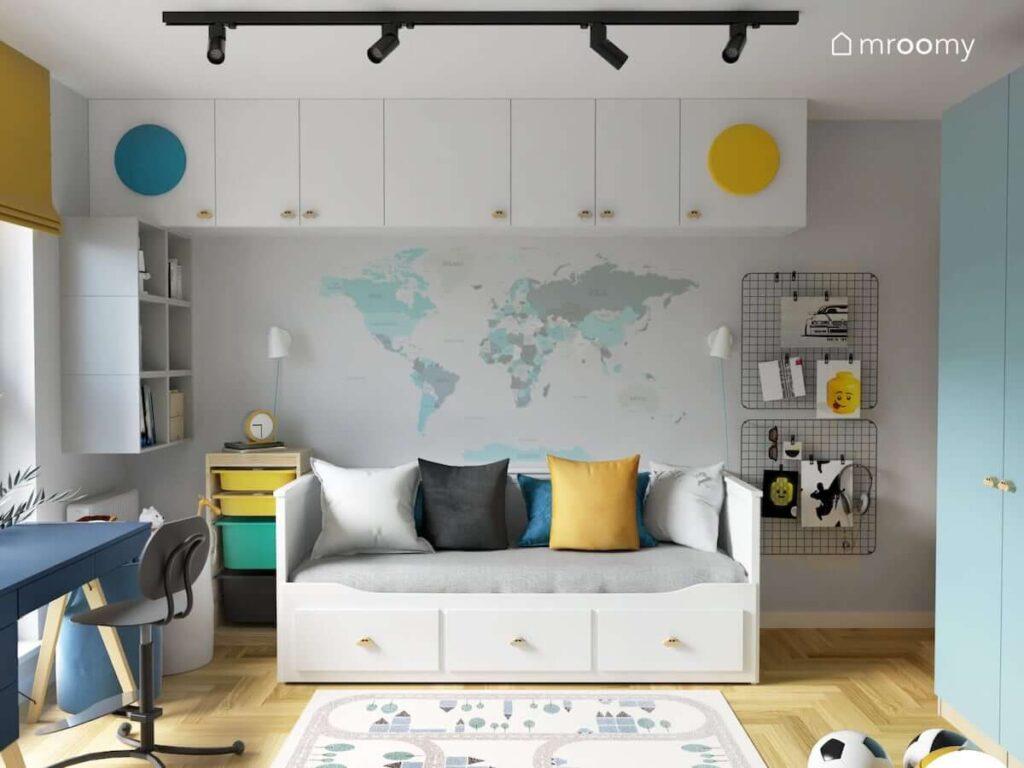 Białe łóżko leżanka z trzema szufladami regał z kolorowymi pojemnikami oraz modułowe szafki a na ścianie organizery ścienne i naklejka w kształcie mapy świata w pokoju dla chłopca