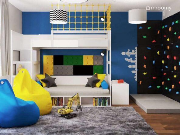 Biało szare łóżko piętrowe z kolorowymi poduszkami oraz panelami ściennymi w kształcie klocków i żółtą siatką zabezpieczającą a także czarna ścianka wspinaczkowa z kolorowymi uchwytami w pokoju dla chłopca