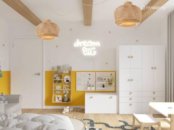 Biało żółty pokój dla chłopca a w nim białe szafki z drewnianymi gałkami drewniana biblioteczka organizery ścienne ledon w kształcie napisu i bambusowe lampy