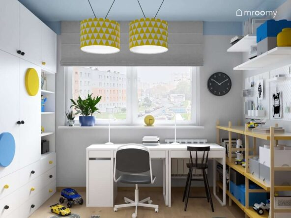Strefa nauki w pokoju dla dwóch chłopców z białymi biurkami i krzesłami a obok regał półki ścienne i organizery w pokoju dla dwóch chłopców