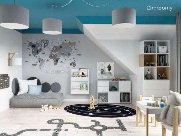 Biało niebieski pokój dla dwóch chłopców z białymi szafkami dużą kwadratową pufą mapą świata na ścianie a na podłodze z galaktycznym dywanem i naklejką w kształcie jezdni