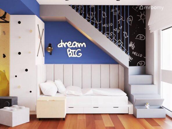 Białe łóżko z szufladami a nad nim panele ścienne i ledon w kształcie napisu oraz ściana pomalowana farbą tablicową w pokoju dwóch chłopców